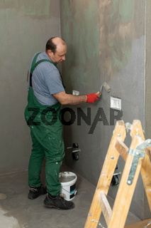 An experienced construction worker applies damp insulation with a paint roller to the wall.