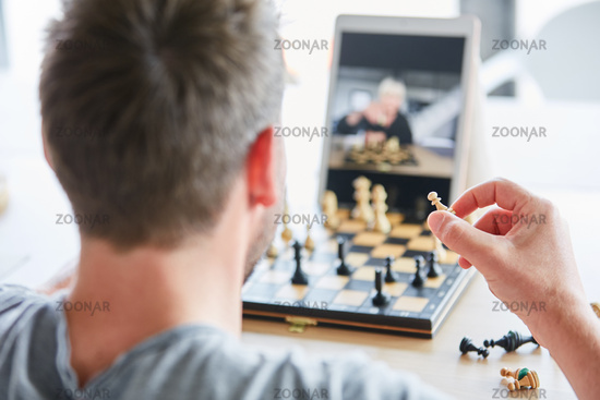 Man holding a chess piece in his hand playing chess