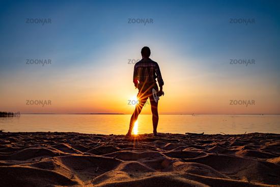 Woman at sunset holding a ukulele