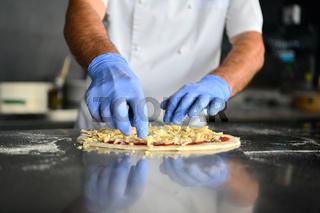 chef  with protective coronavirus face mask preparing pizza