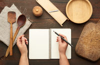 open notebook with blank white sheets and kitchen utensils on a brown wooden table