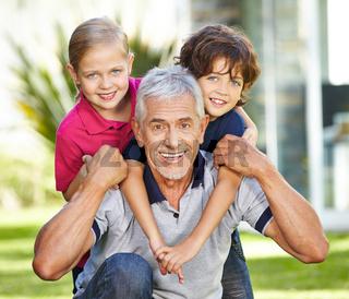 Opa mit zwei Enkeln im Garten