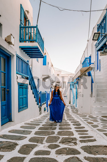 Mykonos Greece, woman on vacation at the Greek Island Mykonos, girl in dress at the white streets of little venice Mykonos