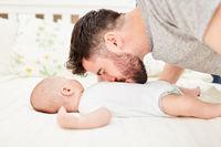 Stolzer Vater küsst Baby auf den Bauch