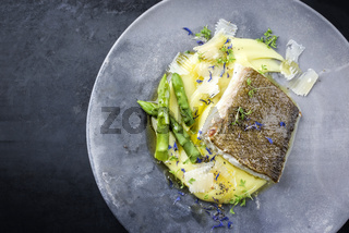 Traditional fried skrei cod fish filet with green asparagus tips and mashed potato creme in parmesan olive oil sauce as top view on a modern design plate with copy space left