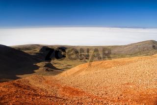 Scenic view of vast white salt plane Salar de Uyuni from colored mountains