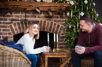 Happy couple sitting near fireplace and Christmas tree