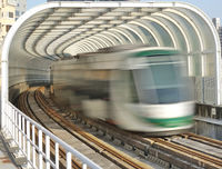 A light rail train emerges from a tunnel with transparent panels