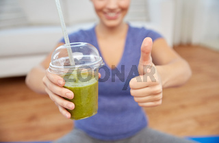 happy woman with cup of smoothie showing thumbs up