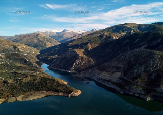 Aerial photography rocky snow-capped Sierra Nevada mountains Embalse de Canales Reservoir in Guejar Sierra, province of Granada, Andalusia, Spain. Picturesque landscape view above. Spain