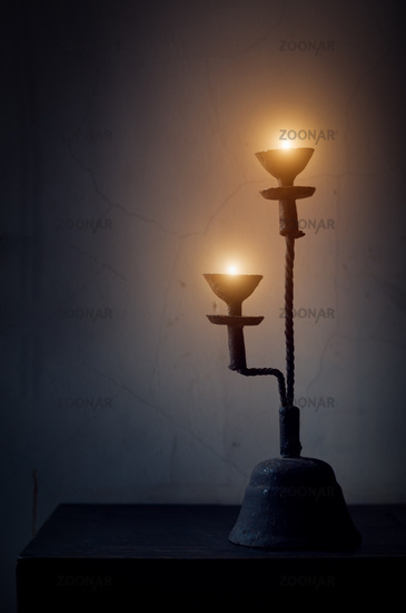 Aged candlestick with warm candle light in dark corner