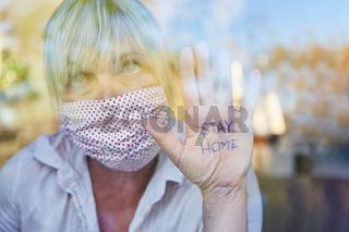 Seniorin hält Hand mit Stay Home Botschaft ans Fenster bei Coronavirus Pandemie