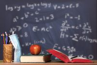 Back to virtual school background concept with stack of books, apple and face mask against math background