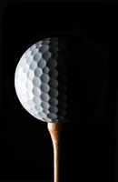 Golf Still Life. Closeup low key golf ball on wood tee with strong side light, against a black backg