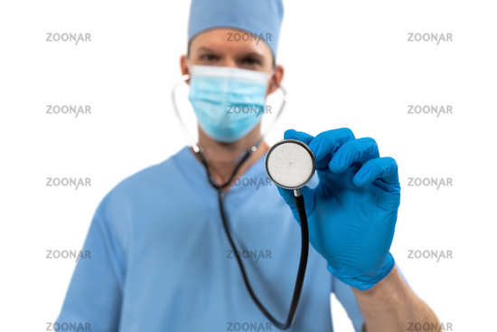 Portrait of male surgeon wearing face mask holding stethoscope against white background