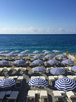 sun beds and umbrellas at beach in nice, france -