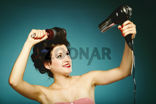 sexy girl in curlers with hairdryer styling hair
