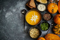 Delicious pumpkin soup with cream, seeds, bread and fresh herbs in elegant ceramic black bowl