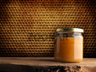 An organic honey jar on a rustic wooden table against a honeycomb background with space for text.