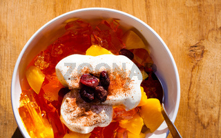 Fruit jelly in bowl with whipped cream and raisin