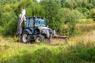 Bulldozer working at the countryside in summer day
