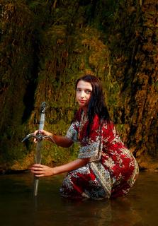 Woman with sword in lake near waterfall.