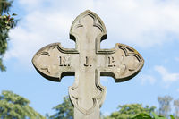 stone cross in front of a cloudy sky on a historical cemetery in germany
