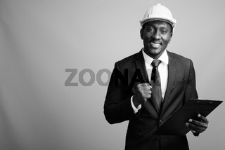 Young handsome African businessman with hardhat against gray background