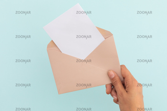 Hand of caucasian woman holding opened envelope with letter over pale blue background