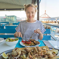 Beautiful female tourist eating delicious sea food on summer vacation in traditional croatian costal restorant by the sea