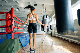 Back view of fitness woman skipping rope in gym