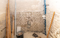 Construction site of a bathroom under construction with wooden slats, spirit level and bucket