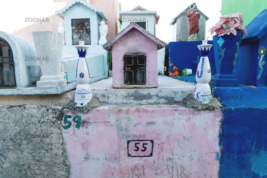 Typical Mexican tombstones with tequilla bottles as decoration in a graveyard in Valladolid, Yucatan