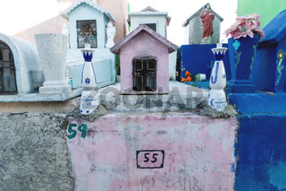 Typical Mexican tombstones with tequilla bottles as decoration in a graveyard in Valladolid, Yucatan, Mexico