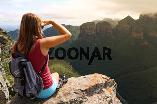 female hiking tourist sitting on mountains and enjoying the view