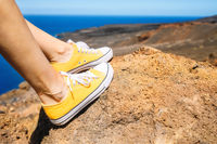 Woman Relaxed, Enjoying Landscape. Traveler Sitting On Rock wearing yellow sneakers. Summer Vacation. Close up.