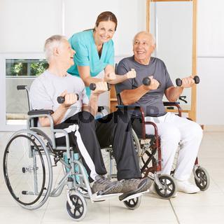 Physiotherapeutin mit zwei Senioren im Rollstuhl
