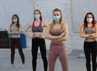 yoga during pandemic wearing medical face protective mask athletic girls in sports out fits standing in yoga class, standing one after another. Group of young sporty people practicing yoga lesson