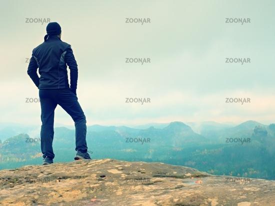 Foggy rocks. Hiker kin black on sharp cliff of sandstone rock