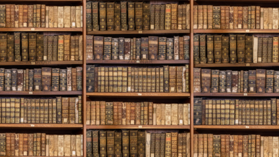 Defocused shelves of old antique books for background in video conference sized to 16 by 9
