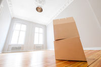 cardboard box in empty room, moving in new flat