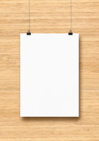 White poster hanging on a wooden wall with clips