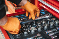 A set of tools for repair in car service - mechanic's hands, close up