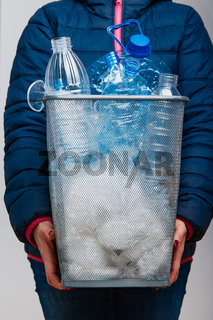 Woman holding trash bin with collected used plastic bottles and packagings