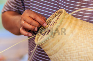 Close up hands weaving bamboo steamer in northeastern village of Thailand