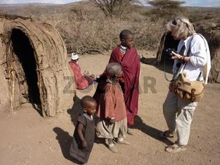 Female tourist talks to Masai children near village mud huts, Tanzania