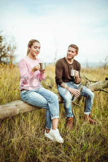 Tea party or coffee drinking outdoors. Cheerful couple drink hot coffee or tea communicate sitting on a wooden log outdoors