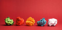 Colorful crumpled paper balls on a red studio background