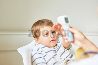 Ängstliches Kind mit Grippe beim Fieber messen
