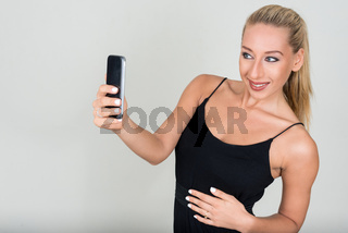 Portrait of young beautiful blonde woman taking selfie